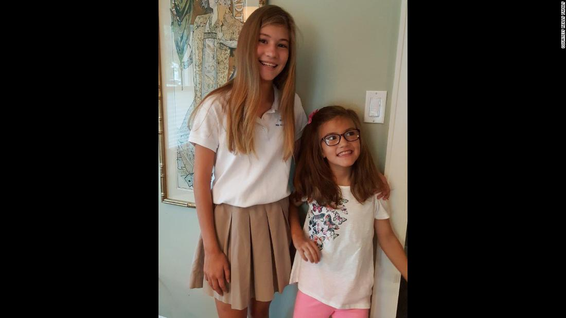 "Avery and her sister Presley took a first-day-of-school photo in August 2016. Presley helped Avery stand up by leaning her against the wall.  ""Avery loves school and was so excited to be heading back to school after her August break,"" her father said."
