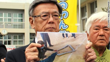 Okinawa Governor Takeshi Onaga stands outside an elementary school as he shows a picture of the window that fell from a US military helicopter.