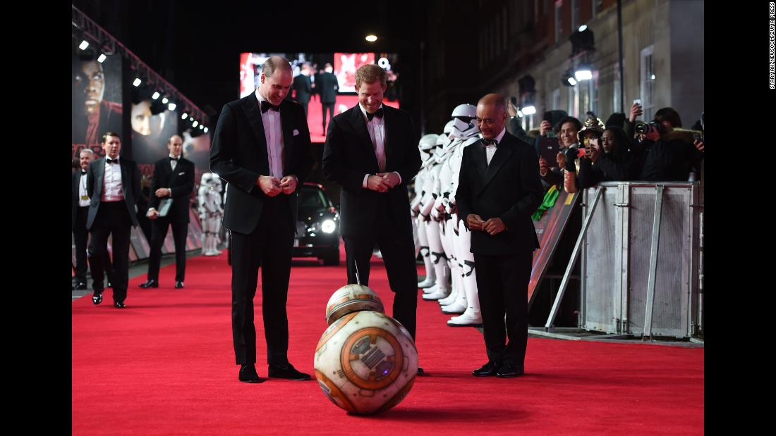 "Britain's Prince William, left, stands next to his brother, Prince Harry, as they watch a BB-8 droid bow to them at the London premiere of ""Star Wars: The Last Jedi"" on Tuesday, December 12."