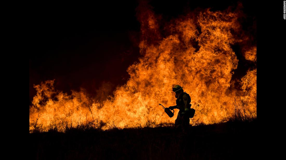 "A firefighter works in Ojai, California, where the Thomas wildfire continued to rage on Saturday, December 9. The Thomas Fire, <a href=""http://www.cnn.com/2017/12/14/us/california-fires/index.html"" target=""_blank"">one of six major wildfires burning in Southern California,</a> is already the fourth-largest in state history, according to CalFire."
