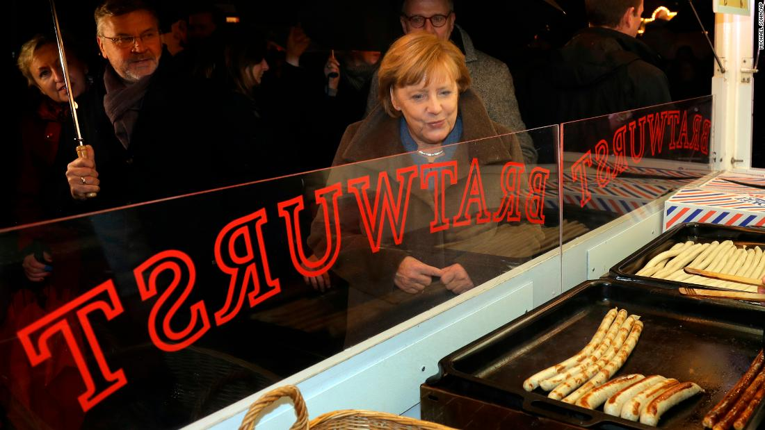 "German Chancellor Angela Merkel leaves a sausage stall as she visits a Christmas market in Berlin on Tuesday, December 12. The market was the site of <a href=""http://www.cnn.com/2016/12/20/europe/berlin-christmas-market-attack-witnesses/index.html"" target=""_blank"">a deadly terrorist attack</a> one year ago."