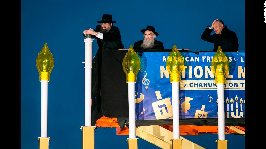Rabbi Levi Shemtov, left, helps during the National Menorah Lighting in Washington on Tuesday, December 12. Hanukkah ends on December 20 this year.