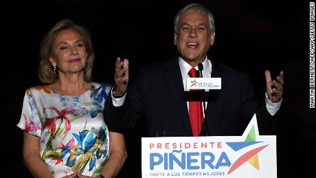 Chilean presidential candidate Sebastian Pinera (R), next to his wife Cecilia Morel, publicly celebrates his victory in Santiago after the runoff election on December 17, 2017. Conservative billionaire Sebastian Pinera will return as Chile's president, the election results show. His rival, leftist challenger Alejandro Guillier, a TV presenter turned senator who ran as an independent but was backed by outgoing center-left President Michelle Bachelet, recognized his defeat.  / AFP PHOTO / Martin BERNETTI        (Photo credit should read MARTIN BERNETTI/AFP/Getty Images)