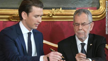 Austrian President Alexander Van der Bellen (R) and Austrian Chancellor of the conservative People's Party Sebastian Kurz sign the letter of appointment during an inauguration ceremony on December 18, 2017.