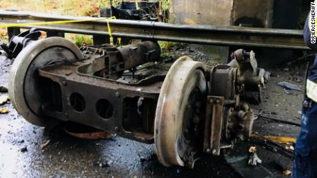 Part of the train chassis sits stripped on the highway.