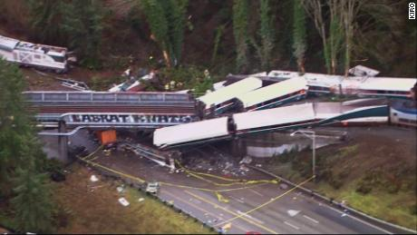 Aerial images show the train sprawled across the track and highway on Monday.