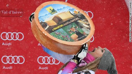 TOPSHOT - US Lindsey Vonn holds a cheese as she celebrates on the podium after winning the women's Super-G race at the FIS Alpine Skiing World Cup in Val-d'Isere, French Alps, on December 16, 2017. / AFP PHOTO / PHILIPPE DESMAZES        (Photo credit should read PHILIPPE DESMAZES/AFP/Getty Images)