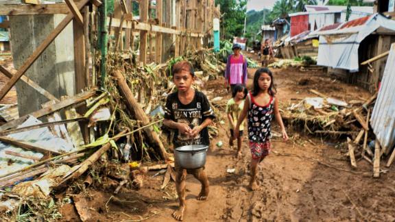 Children walk past debris and damaged houses trees in Barangay San Mateo Borongan in eastern Samar on December 17, 2017.