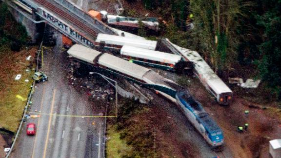 Cars from an Amtrak train that derailed above lie spilled onto Interstate 5, Monday, Dec. 18, 2017, in DuPont, Wash. The Amtrak train making the first-ever run along a faster new route hurtled off the overpass Monday near Tacoma and spilled some of its cars onto the highway below, killing several people, authorities said. (AP Photo/John Froschauer)