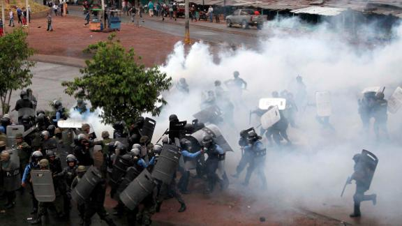Police stand amid tear gas as they clash with supporters of opposition presidential candidate Salvador Nasralla in Tegucigalpa, Honduras, Monday, Dec. 18, 2017.