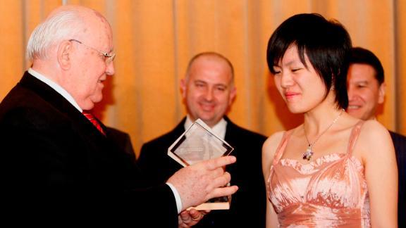 Hou receives the World Women's Chess Champion trophy from former Soviet Union President Mikhail Gorbachev in November 2011.