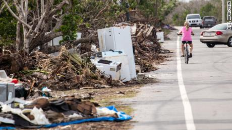 A cyclist passes the mounds of trash still littering the sides of roads in the Florida Keys.