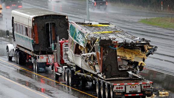 Two damaged train cars sit on flatbed trailers after being taken away from the scene on December 19. When it derailed, the train was going 80 mph in a 30 mph zone. Federal investigators said they don't know why yet.