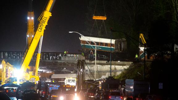 A train car is lifted away on Tuesday, December 19, the day after an Amtrak passenger train derailed near DuPont, Washington. Several of the train