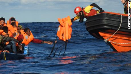 A rescuer hands out life jackets to migrants stranded in the Mediterranean.