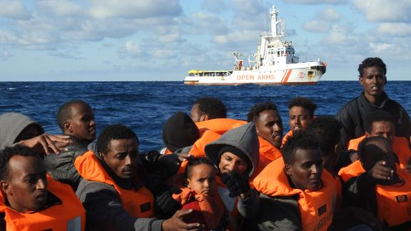 Rescued migrants wait to board the Open Arms.