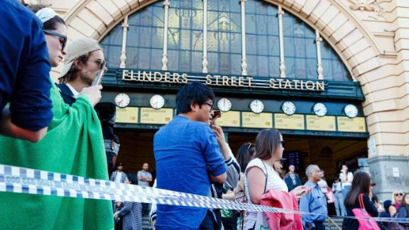 People gather at the scene of where a car ran over pedestrians in Flinders Street in Melbourne on December 21, 2017.