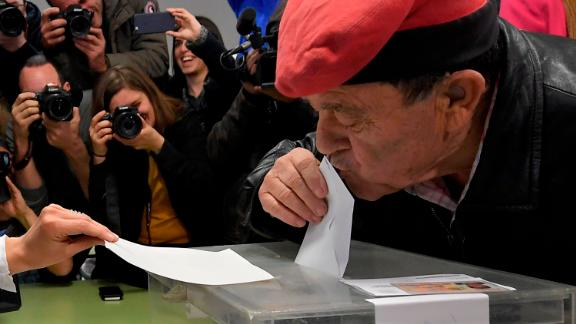 A man wearing an Catalan barretina hat kisses his ballot before casting his vote for the Catalan regional election at a polling station in Barcelona on December 21, 2017.