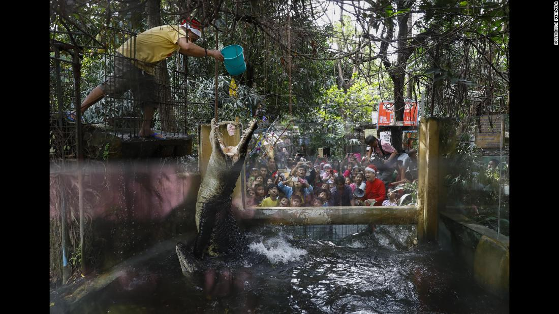 A zoo staff member feeds crocodiles as visitors look on at the Malabon Zoo in Malabon, Philippines, on Thursday, December 21. Owner Manny Tangco -- bottom right, holding a megaphone and wearing a Santa Claus hat -- held a Christmas event at the zoo and gave select visitors a tour ahead of the holidays.