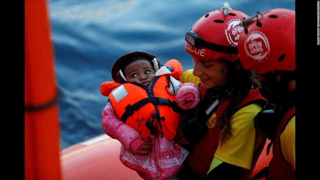 A crew member of MV Open Arms, the search and rescue ship of Proactiva Open Arms, carries a migrant baby during a mid-sea transfer of migrants in the central Mediterranean, off the coast of Libya, on Saturday, December 16. The baby was being passed to crew members of MV Aquarius, a search and rescue ship run in partnership between SOS Mediterranee and Médecins Sans Frontières.