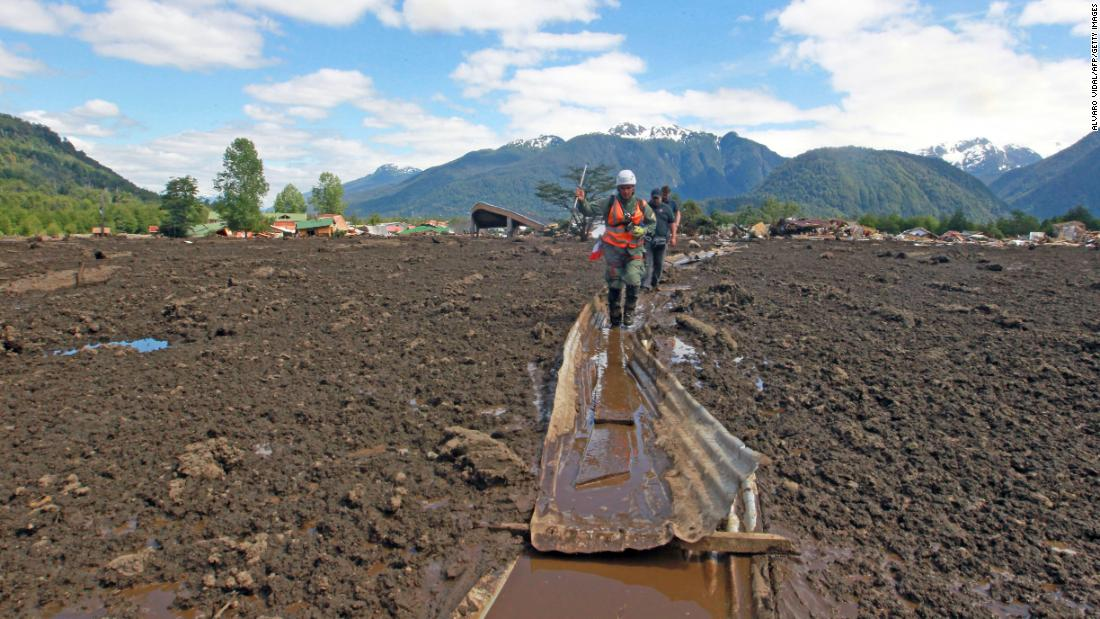 "A rescue worker walks over mud in Villa Santa Lucia, near Chaitén in southern Chile, <a href=""http://www.cnn.com/2017/12/17/americas/chile-landslide-intl/index.html"" target=""_blank"">after a landslide</a> caused by heavy rains devastated the area on Monday, December 18. At least five people were killed and 15 are still missing after the landslide swept through the remote village, the country's president said."