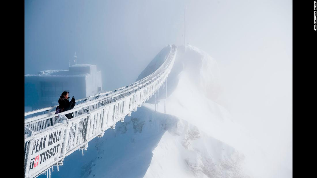 "A tourist takes a photo from the ""Peak Walk"" suspension bridge in the Swiss Alps on Wednesday, December 20. The bridge, which is 107 meters long and 80 centimeters wide (about 351 feet long and 31 inches wide), is one of the world's first and connects two mountain peaks."