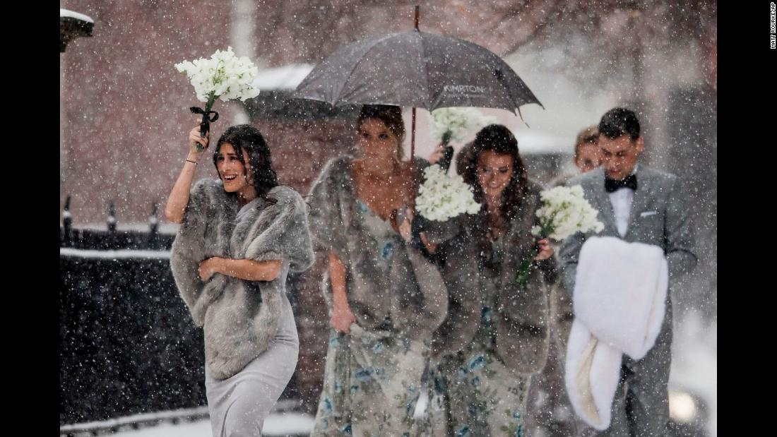 A bridal party makes its way through a snowstorm in Philadelphia on Friday, December 15.