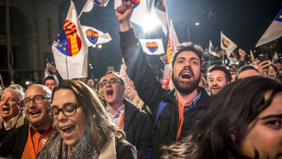 Supporters wave flags and banners at the Ciutadans party headquarters as they celebrate the results of the election Thursday.