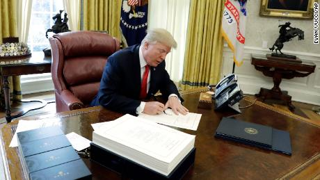 Trump signs tax bill before leaving for Mar-a-Lago