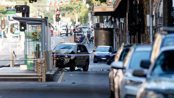 A white SUV sits in the middle of the road as police and emergency personnel work at the scene of where a car ran over pedestrians in Flinders Street in Melbourne on December 21, 2017.