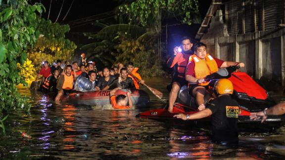 Rescue workers evacuate residents in Davao on the southern Philippine island of Mindanao early on the morning of December 23.