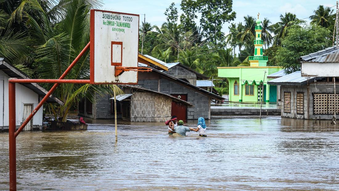 Evacuees walk through floodwaters to a safer place in Kabacan on the island of Mindanao on December 23.