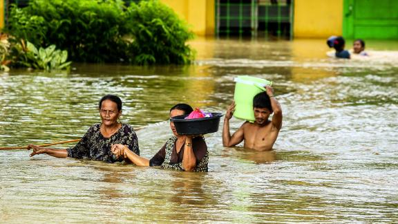 Residents maneuver floodwaters on Mindanao on December 23.