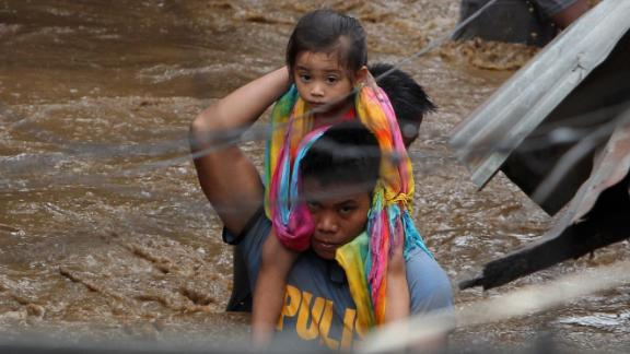 A police officer carries a young girl on a flooded street in Cagayan de Oro on Friday, December 22.