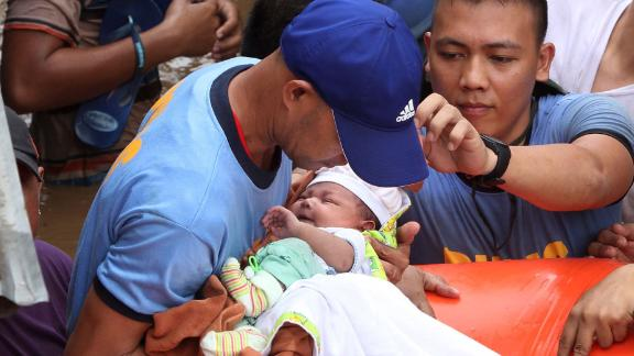 Police evacuate a baby in Cagayan de Oro on December 22 after heavy rains resulting from Tembin.
