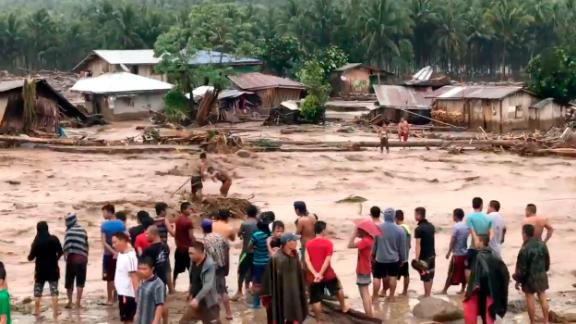 Villagers cross raging floodwaters December 22 in Lanao del Norte province in the southern Philippines in this photo made from video by Aclimah Disumala.