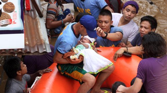 Police officers evacuate a baby Friday in Cagayan de Oro after Tropical Storm Tembin hit.