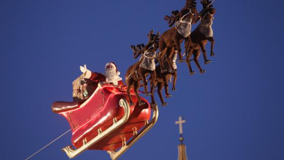 An actor dressed as Santa Claus waves from a suspended sleigh over a Christmas market as the Dom cathedral stands behind on November 25, 2013 in Berlin, Germany. Christmas markets, which traditionally sell mulled wine, stollen cake, Christmas tree ornaments and other crafts and are an essential part of German Christmas tradition, open across the country this week.
