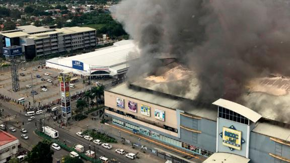 In this photo provided by Special Assistant to the President Christopher Bong Go, a fire rages at  shopping mall in Davao city, the hometown of Philippine President Rodrigo Duterte, on Saturday, December 23 in southern Philippines.