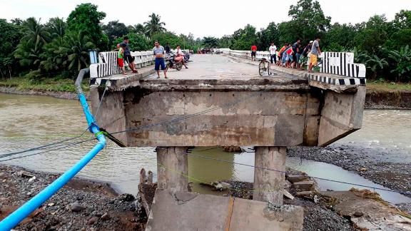 People gather on a bridge which was damaged by flooding Sunday, December 24, after Tropical Storm Tembin dumped heavy rains on the area.