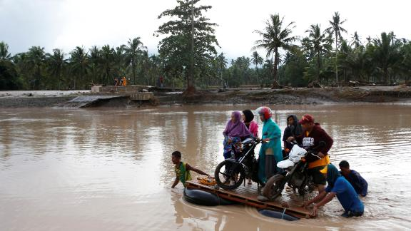 Filipino villagers cross a river on makeshift rafts in the town of Salvador, Lanao del Norte province, December 23.