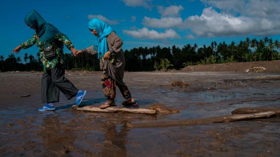 Residents walk through mud on  December 25 in Salvador, Lanao del Norte province, after Tembin swept the southern Philippines. Tembin is the nation