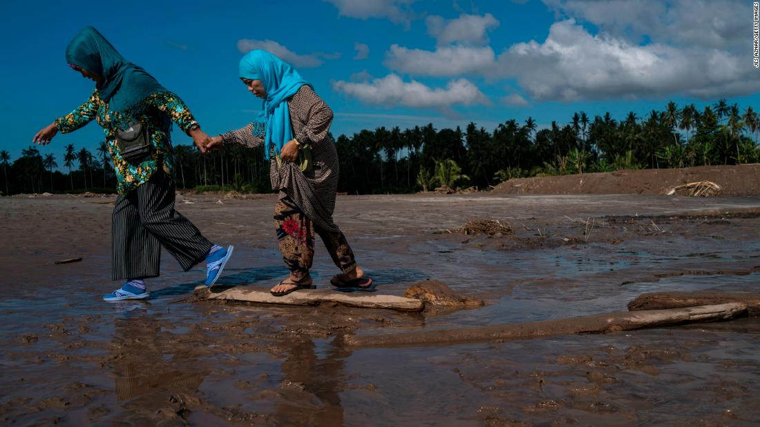 Residents walk through mud on  December 25 in Salvador, Lanao del Norte province, after Tembin swept the southern Philippines. Tembin is the nation's second deadly tropical storm this month.