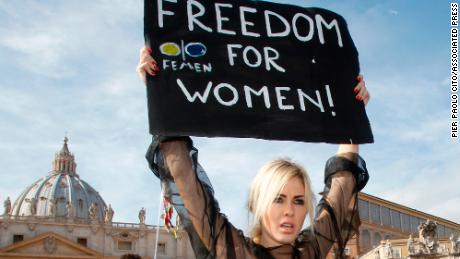 "An activist of the Ukrainian female rights organization ""Femen"" shows a placard during a protest in St. Peter's Square at the Vatican, Sunday, Nov. 6, 2011. (AP Photo/Pier Paolo Cito)"