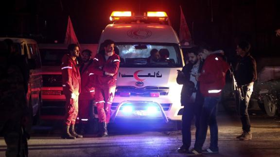 Syrian staff from the International Committee of the Red Cross take part in an evacuation operation in Douma in the eastern Ghouta region on the outskirts of the capital Damascus late on December 26, 2017.Aid workers have begun evacuating emergency medical cases from Syria