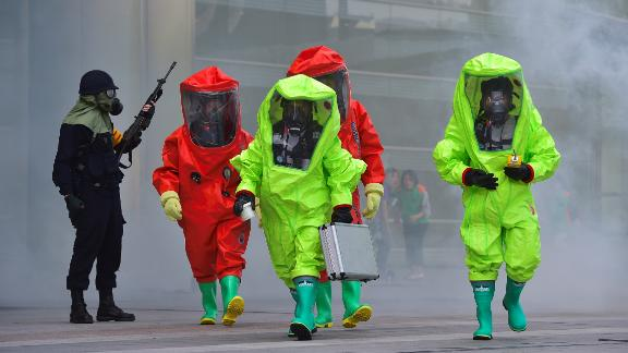 South Korean rescue workers wearing chemical protective suits participate in a disaster management exercise at the COEX shopping and exhibition center in Seoul on May 20, 2016.