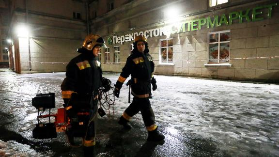 Firefighters outside a Perekrestok supermarket in St. Petersburg where an explosion injured 10 people.