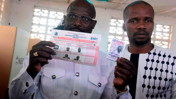 Football icon and candidate for the president election for the Coalition for Democratic Change (CDC) party, George Weah (L) presents his voting ballot and identification card for the second round of presidential elections on December 26, 2017 at a polling station in Monrovia.  Liberians go to the polls in a run-off presidential election on December 26 between Vice President Joseph Boakai and footballing icon George Weah, a vote that will mark the country's first democratic transition since 1944. / AFP PHOTO / SEYLLOU        (Photo credit should read SEYLLOU/AFP/Getty Images)