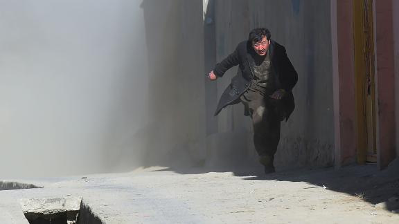 An Afghan man runs away as dust blows in the aftermath of the third blast at a Shiite cultural centre in Kabul on December 28, 2017.At least 40 people were killed and dozens more wounded in multiple blasts at a Shiite cultural centre in Kabul on December 28, officials said, in the latest deadly violence to hit the Afghan capital. / AFP PHOTO / SHAH MARAI        (Photo credit should read SHAH MARAI/AFP/Getty Images)