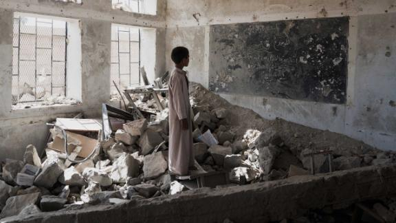 A student stands in the ruins of one of his former classrooms, which was destroyed in June 2015, at the Aal Okab school in Saada, Saada Governorate, Yemen, Monday 24 April 2017. Students now attend lessons in UNICEF tents nearby,